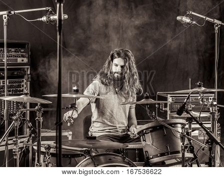 Photo of a young male drummer with long hair playing his drum set.