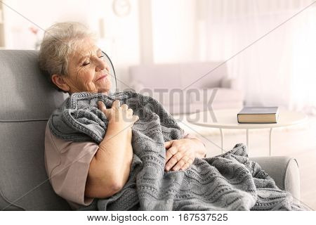 Depressed elderly woman sitting in arm-chair at home