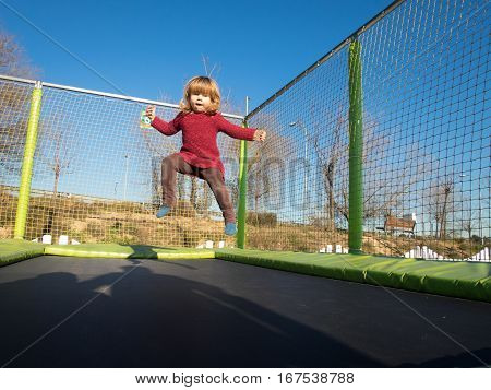 Little Child Jumping On Trampoline