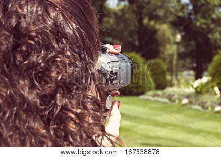 Girl taking photo with digital mirror camera closeup shot colorized toned image.