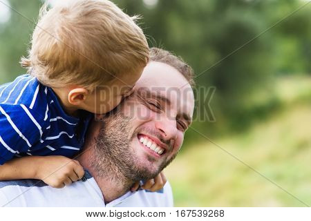 Child playing with his father. Child kissing father. Daddy playing active games with his son outside. Happy family portrait. Laughing dad with little boy enjoying nature together.