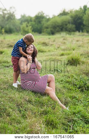 Boy kissing his pregnant mother. Happy mother and her son
