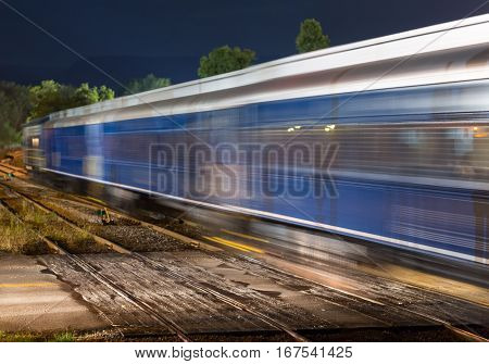 Blurred railway carriages move fast past a deserted railroad crossing with the headlights of a waiting car illuminating the train