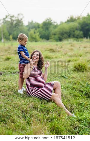 Pregnant mother and her son playing together. Happy mother and her son