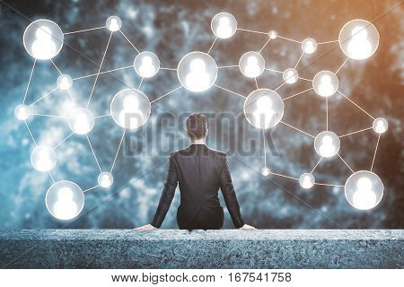 Businessperson on rooftop looking at people icons. Human resources concept