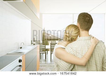 Back view of cuddling caucasian couple in bright kitchen interior. They are thinking about the future of their family