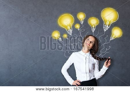 Daydreaming caucasian girl on concrete background with creative lamp drawings. Ideas concept