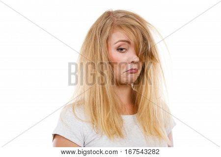 Bad hairstyle concept. Sad blonde woman with messy hair looking tired and dissatisfied. Studio shot on white background.