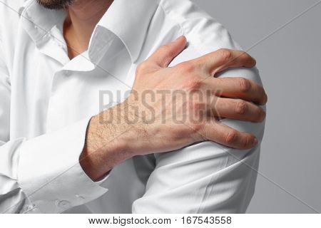 Man suffering from pain in shoulder on color background, closeup