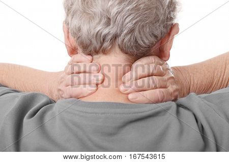 Elderly woman suffering from neck pain on white background, closeup
