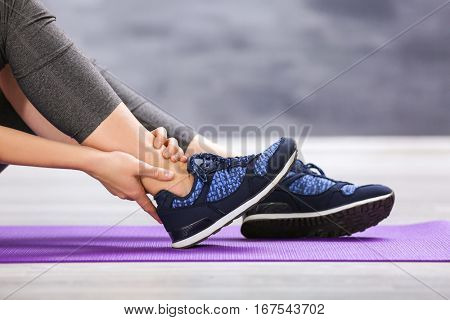 Young woman suffering from pain in ankle while sitting on stretching mat indoors