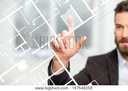 Architect or designer working with plan drawing on the virtual screen standing in the white room