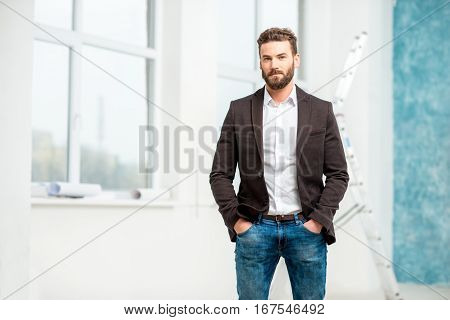Portrait of handsome architect or designer standing in the white room