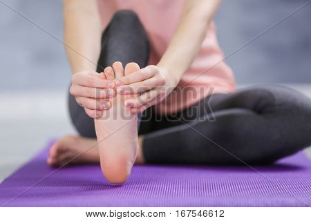 Young woman suffering from pain in foot while sitting on stretching mat, close up