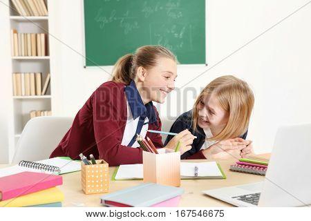 Two cute girls sitting at desk in school class