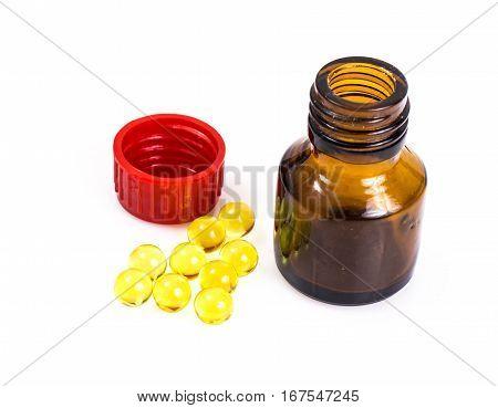 Drugstore Vitamins: round gelatin capsules in a bottle of dark glass. Studio Photo