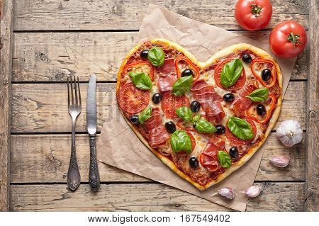 Pizza heart shaped love concept Valentine's Day romantic dinner food with knife and fork. Prosciutto, olives, tomatoes, parsley, basil and mozzarella cheese meal served on vintage wooden table