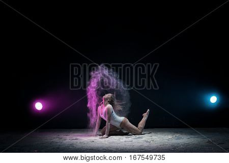 Female sexy gymnast in beige bodysuit bending gracefully on black background with colored dust all over body shot made with color filters