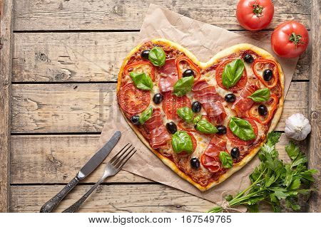 Pizza heart love Valentine's Day romantic dinner food served with knife and fork. Prosciutto, olives, tomatoes, parsley, basil and mozzarella cheese meal on vintage wooden table