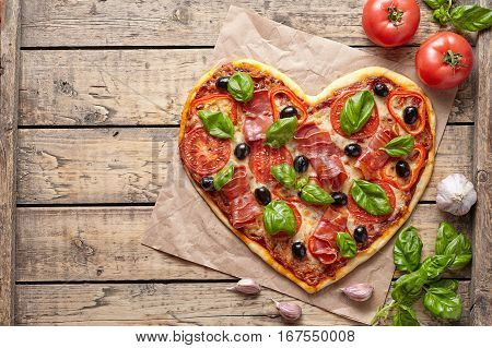 Pizza heart love Valentine's Day romantic Italian restaurant dinner food. Prosciutto, olives, tomatoes, parsley, basil and mozzarella cheese meal on vintage wooden table