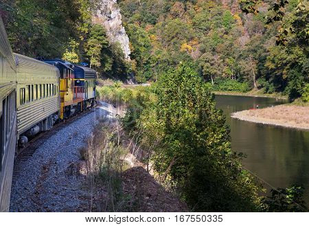 Diesel locomotive engine on steep trip into mountains of West Virginia with fisherman in the calm river below the tracks