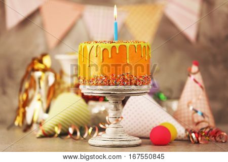 Delicious cake with happy birthday candle on festive background