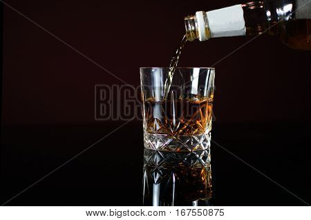 Pouring Bourbon whiskey into glass. Black table with reflection.