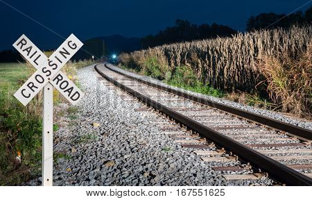 Sign for railroad crossing with Diesel locomotive engine coming towards the tracks in the mountains of West Virginia
