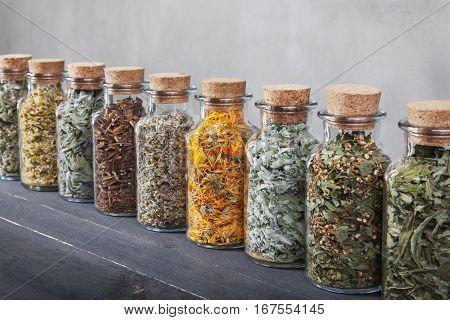 Assortment is aligned on a black table. Chamomile, sage, dandelion roots, wormwood, calendula, mint hawthorn fireweed