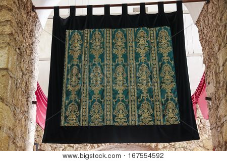 tapestry with embroidered motifs in green and gold