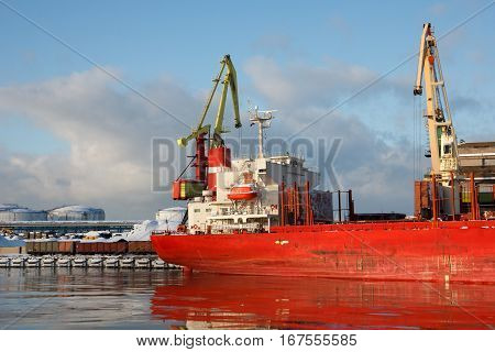 A docked ship being loaded with cargo
