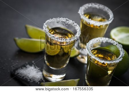 Tequila shot with lime and sea salt on black table