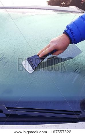 person scraping away the ice from the windshield