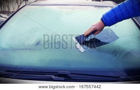 person scrapes away the ice from the windshield