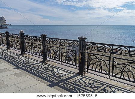 The shadow of the openwork metal fence on the pavement. Quay in the resort town of Sudak Crimea.