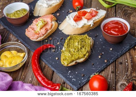 Photo of sandwiches with vegetables on black plank on wooden table