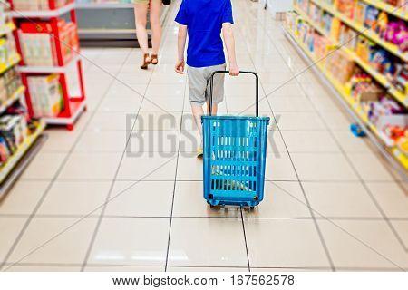 Little child boy holding shopping basket in supermarket store