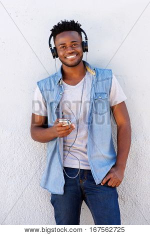 Cheerful Man With Cellphone And Headphones Against White Background