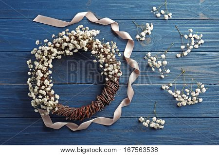 Beautiful floral wreath with satin ribbon on dark wooden background