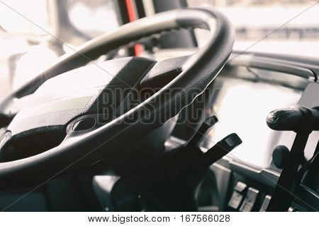 Steering wheel in cabin of big truck, closeup