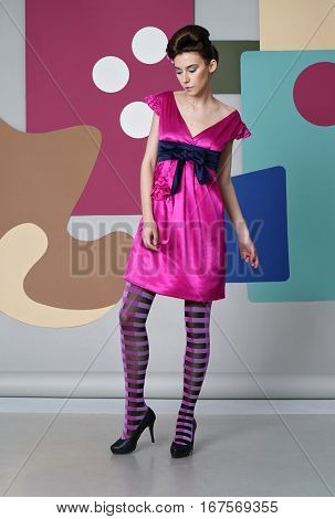 Danish design. Eccentric outfit: bright dress, striped tights, heels. Backdrop: circles, rectangles, Egg chair.