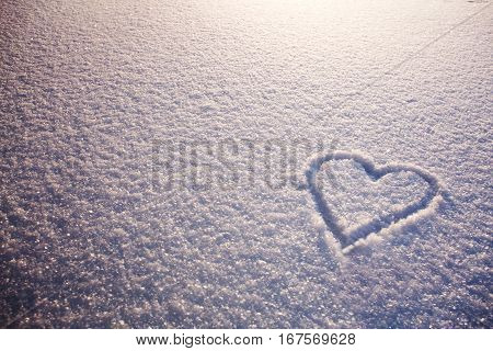 Beautiful romantic background with heart on snow. Snow patterns illuminated by morning sun. Heart drawing on snow. Free space for text on snowy background.