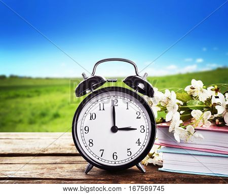 Alarm clock with books and spring blooming branch on wooden table against landscape background. Time change concept