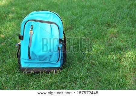 Blue rucksack on green grass