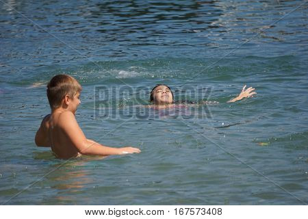 HARBOR SPRINGS, MICHIGAN / UNITED STATES - AUGUST 3, 2016: Children enjoy swimming at the Zorn Park Public Beach near downtown Harbor Springs.