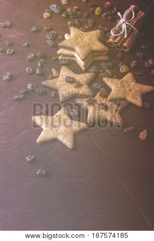 Close up of homemade ginger cookies, cinnamon with raisins on a red wooden table. Copy space. Vertical Retro toned image