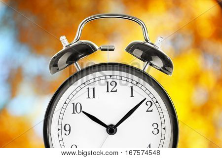 Alarm clock on blurred yellow foliage background. Time change concept