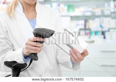 Female cashier scanning barcode on package at shop