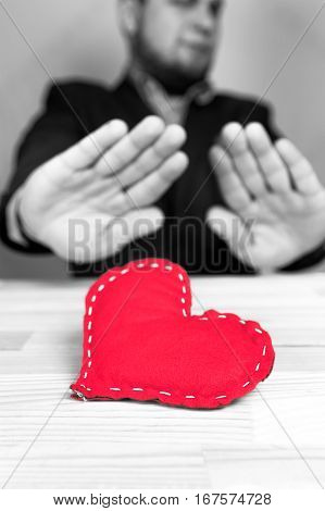 Elegant man in a suit rejecting homemade red heart on Valentine's Day. Natural wooden table. Black and white.