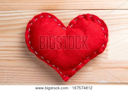 Red homemade heart on natural wooden table on Valentine's Day.
